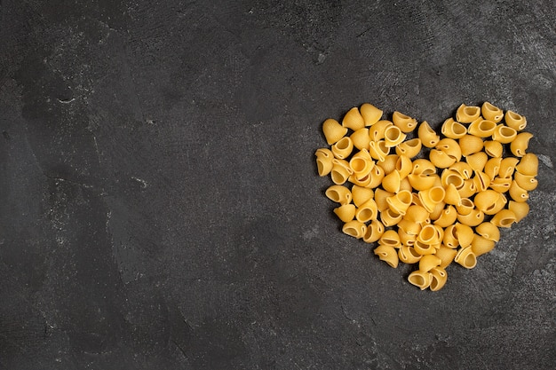 Top view of raw italian pasta heart shaped on the dark surface