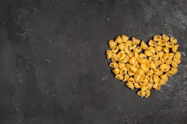 Vista dall'alto di pasta italiana cruda a forma di cuore sulla superficie scura