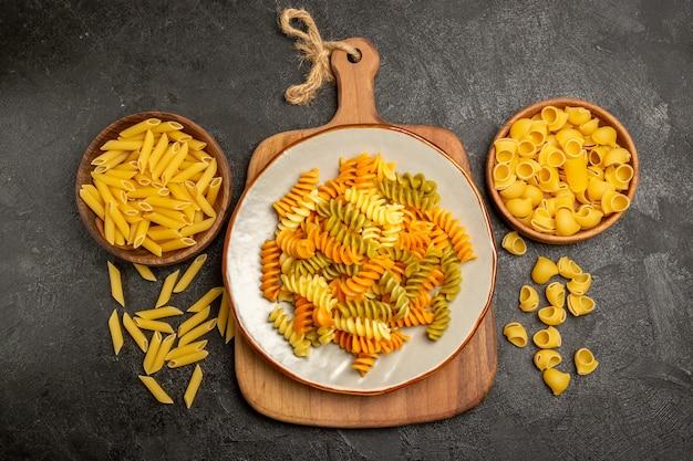 Pasta italiana cruda vista dall'alto all'interno di piatti marroni su grigio scuro