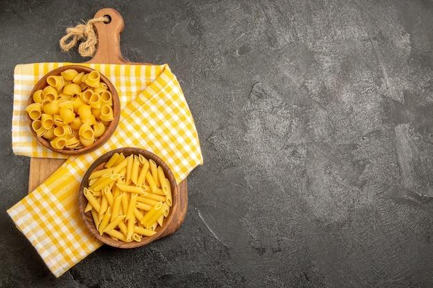 Vista dall'alto pasta italiana cruda all'interno di piatti marroni sul grigio