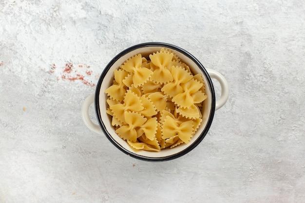 上面図白い背景の上の小さな鍋の中の生のイタリアンパスタ食品食事生の写真