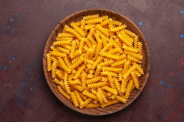 Top view raw italian pasta inside wooden tray on dark background product ingredient meal food vegetable