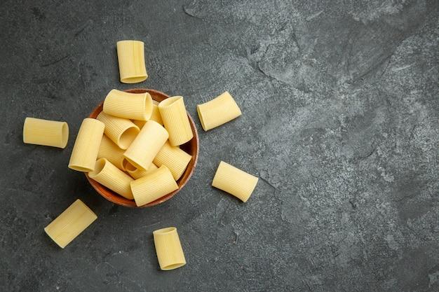 Vista dall'alto pasta italiana cruda poco formata su sfondo grigio pasta alimentare cruda impasto