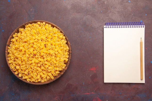 Vista dall'alto la pasta italiana cruda poco formata all'interno della piastra sullo sfondo scuro pasta alimentare pasta cena cruda molti
