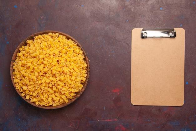 Vista dall'alto la pasta italiana cruda poco formata all'interno della piastra su sfondo scuro pasta pasto alimentare molti