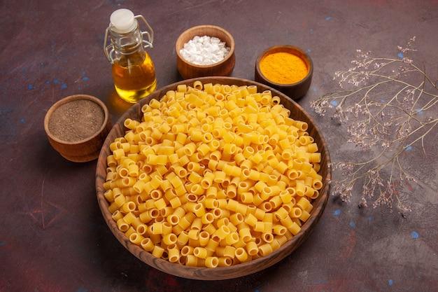 Vista dall'alto pasta italiana cruda poco formata all'interno della piastra sulla scrivania scura pasta alimentare cena pasta cruda molti