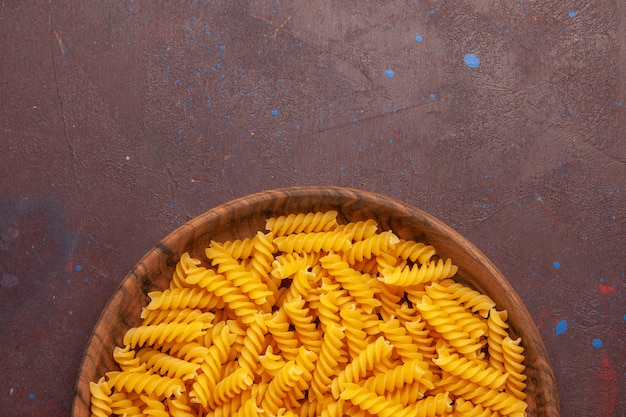 Top view raw italian pasta little formed inside plate on dark desk pasta raw meal food dough