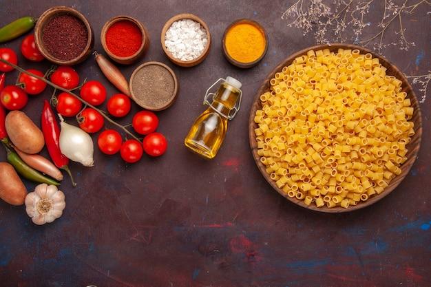 Вид сверху сырые итальянские макароны, маленькие сформированные внутри тарелки на темном фоне, макароны, еда, тесто, ужин, сырые, много