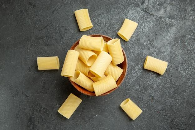 Вид сверху сырые итальянские макароны, немного сформированные на сером фоне, еда, макароны, сырое тесто