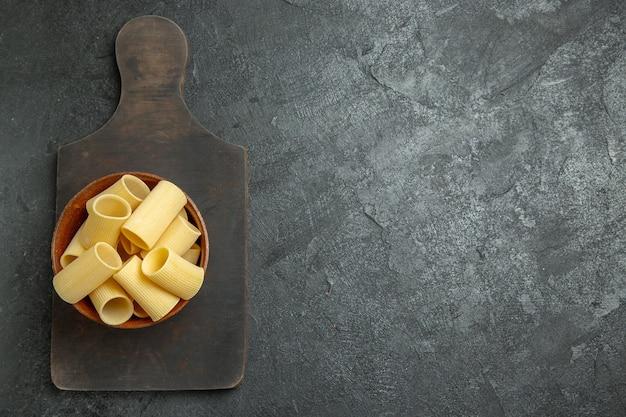 Вид сверху сырые итальянские макароны, немного сформированные на сером фоне, еда, сырые макароны, тесто