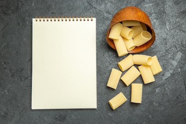 Вид сверху сырой итальянской пасты, немного сформированной на сером фоне, сырая еда, паста, тесто