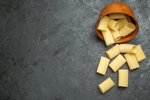 上面図灰色の背景に少し形成された生のイタリアンパスタ生の食事食品パスタ生地