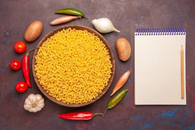 Vista dall'alto pasta italiana cruda poco formata di colore giallo su sfondo viola scuro pasta farina cruda