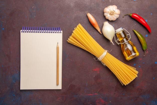 Vista dall'alto pasta italiana cruda formata a lungo su sfondo viola scuro pasto pasta alimentare pasta verdura cruda