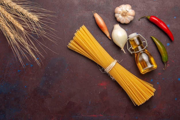 Top view raw italian pasta long formed on dark-purple background meal food dough pasta raw vegetables