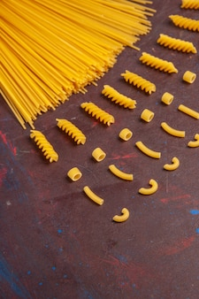 Vista dall'alto pasta italiana cruda lunga formato giallo colorato su sfondo scuro pasta italia pasta pasto crudo cibo
