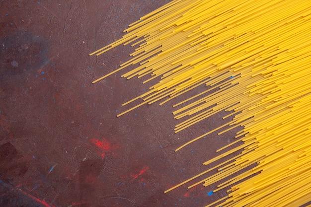 Вид сверху сырые итальянские макароны длинной формы желтого цвета на темном столе макароны италийское тесто пищевой краситель