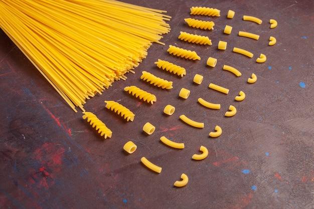 上面図生イタリアンパスタ長い形の黄色い色の暗い机のパスタイタリア生地ミール生食用色素