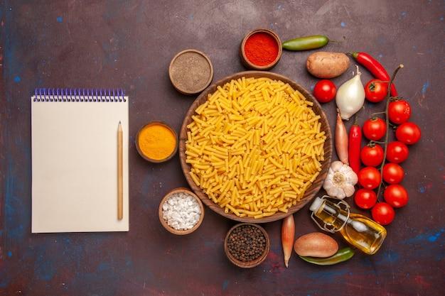 Vista dall'alto pasta italiana cruda con diversi condimenti sull'impasto di colore alimentare di pasta di sfondo scuro