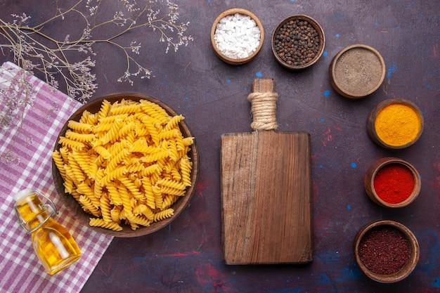 Vista dall'alto pasta italiana cruda con diversi condimenti sul colore degli ingredienti del pasto alimentare pasta superficie scura