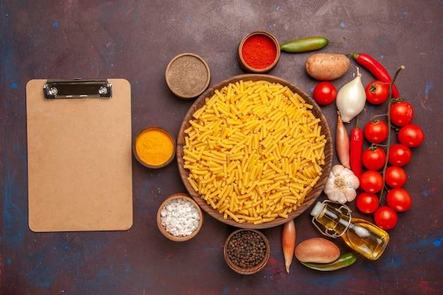 暗い背景のパスタミール食品着色料生地にさまざまな調味料を使用した上面図生イタリアンパスタ