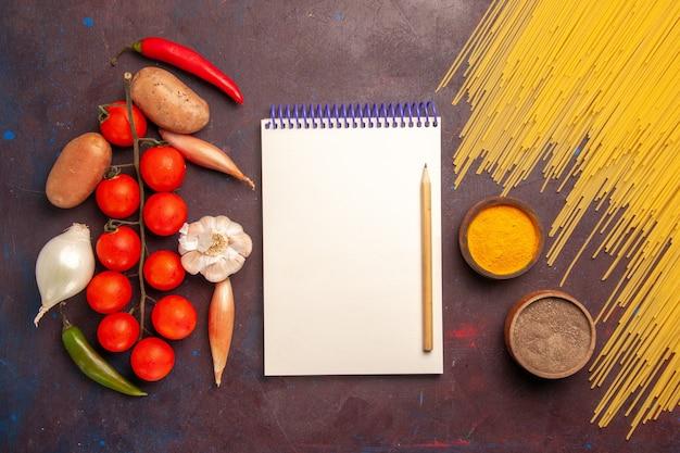 Вид сверху сырой итальянской пасты со свежими овощами и приправами на темном фоне еда паста итальянское тесто пищевой краситель