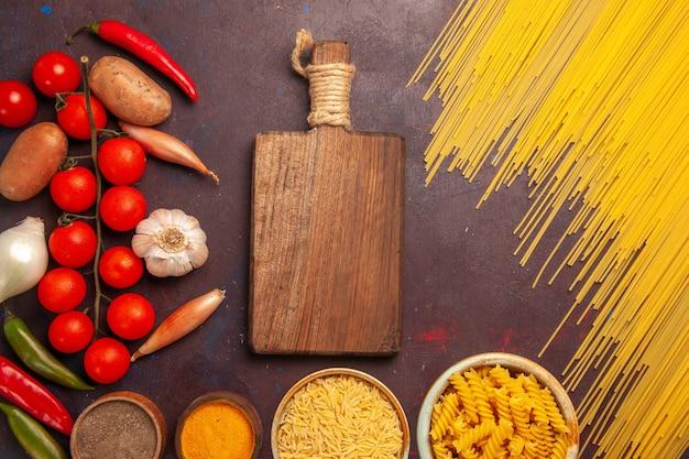 暗い背景に新鮮な野菜と調味料を使ったトップビュー生イタリアンパスタ食事食品生色野菜