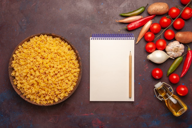暗い背景に新鮮な野菜と生のイタリアンパスタの上面図野菜パスタ食事食品