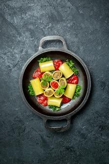 Вид сверху сырые итальянские макароны с мясной зеленью и томатным соусом внутри сковороды на темном фоне еда из теста для макаронных изделий