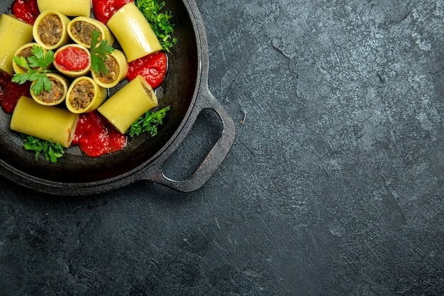 Vista dall'alto pasta italiana cruda con verdure di carne e salsa di pomodoro all'interno della padella sullo sfondo scuro pasta pasta pasto pasto