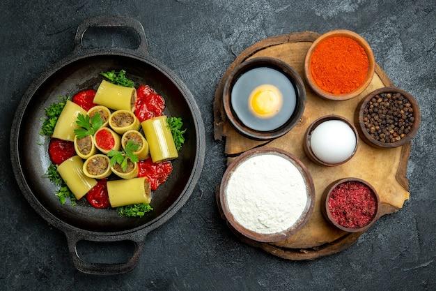 Vista dall'alto pasta italiana cruda con verdure di carne e salsa di pomodoro all'interno della padella sullo sfondo grigio scuro pasta pasta pasto pasto