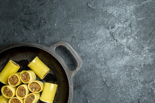 暗い背景の鍋の中に肉が入ったトップビュー生イタリアンパスタパスタ生地ミールフード