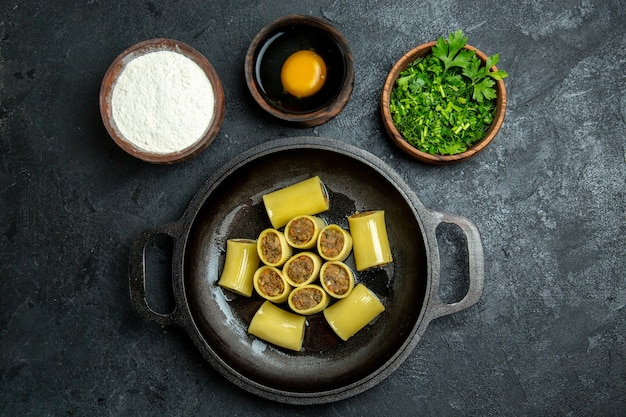 Vista dall'alto pasta italiana cruda con carne all'interno della padella e con verdure su sfondo scuro pasta pasta pasto pasto