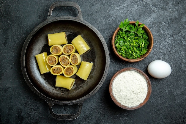 Top view raw italian pasta with meat inside pan and with greens on dark background pasta dough meal food