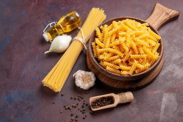 Вид сверху сырые итальянские макароны с луком на темном фоне, еда из теста макаронных изделий