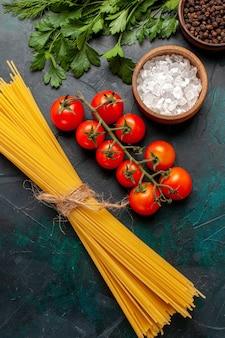 Вид сверху сырой итальянской пасты с приправами и красными помидорами на темной поверхности сырого ингредиента еды еды