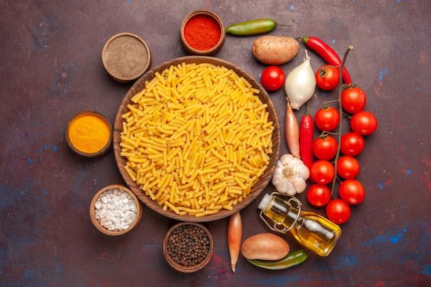 Vista dall'alto di pasta italiana cruda con condimenti su sfondo scuro pasta alimentare colorante pasta