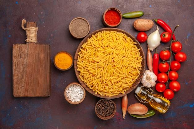 Vista dall'alto pasta italiana cruda con condimenti sulla pasta alimentare farina di pasta scura scrivania