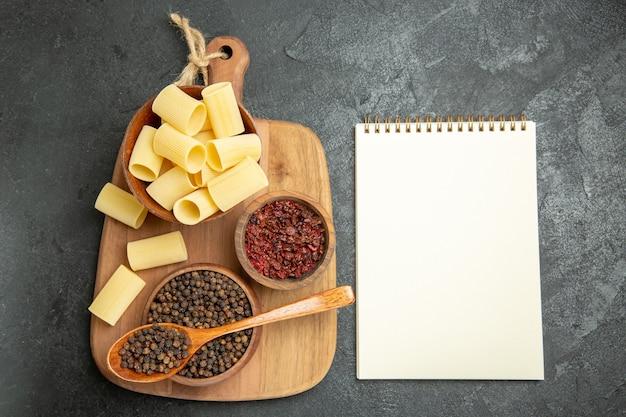 Vista dall'alto pasta italiana cruda con condimenti su sfondo grigio condimenti alimentari pasta pasta pasto piccante