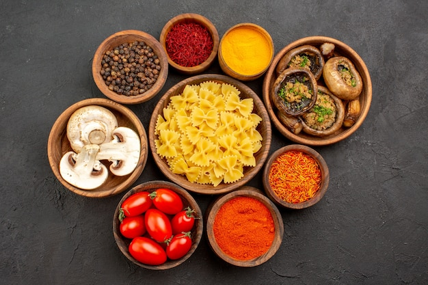 Top view raw italian pasta with seasonings and mushrooms on dark background