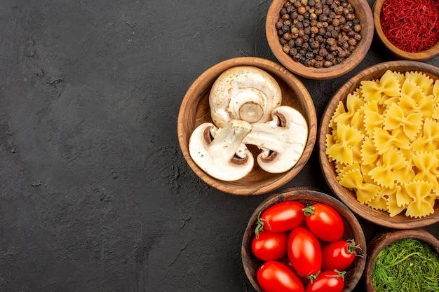 Vista dall'alto pasta italiana cruda con condimenti e funghi sulla scrivania scura