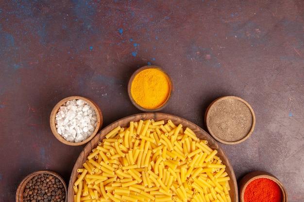 어두운 책상 파스타 식사 음식 색상 반죽에 조미료와 상위 뷰 원시 이탈리아 파스타