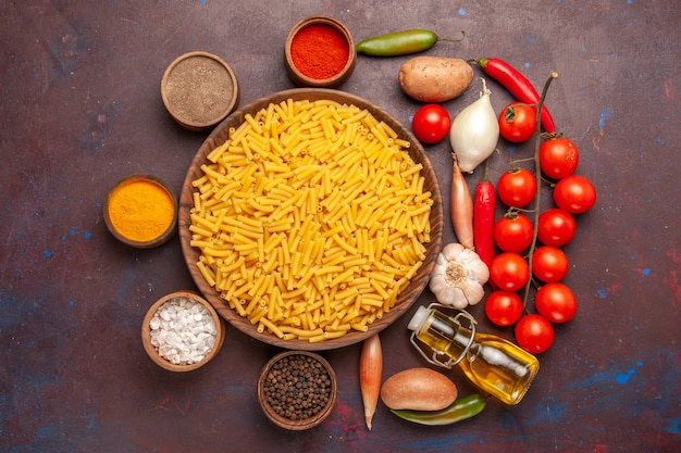 暗い背景に調味料を加えた上面の生イタリアンパスタパスタミール食品着色料生地