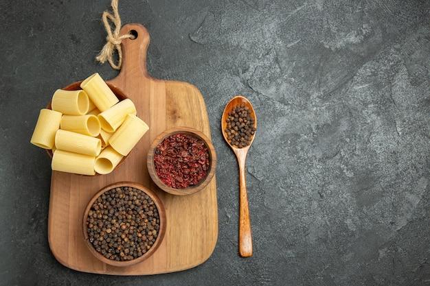 上面図灰色の背景に調味料を入れた生イタリアンパスタ食品調味料パスタ生地ミールスパイシー