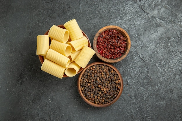 Вид сверху сырые итальянские макароны с приправами на сером фоне паста из теста мука сырые пряные
