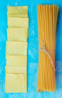 Top view of raw italian spaghetti pasta tied with rope and thinly rolled dough cut into squares on blue background
