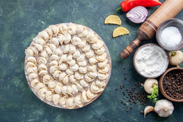 暗い背景に小麦粉と野菜が入った生の小さな餃子の上面図肉生地食品料理カロリー色野菜ミール