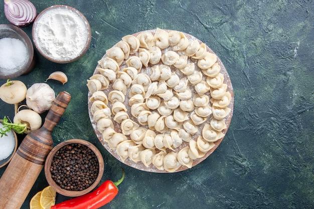 어두운 배경 고기 반죽 음식 접시 칼로리 색상 야채 식사에 밀가루와 야채와 함께 상위 뷰 원시 작은 만두