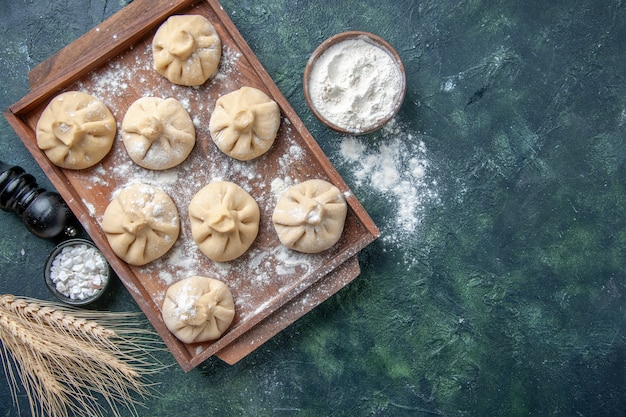 Top view raw little dumplings with meat inside on dark background color meal dish cooking flour dough meat