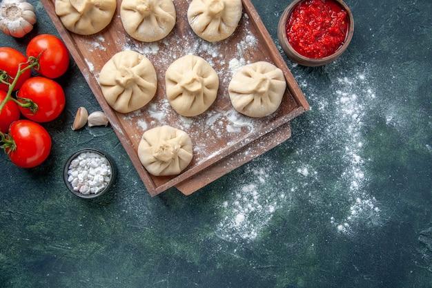 Vista dall'alto gnocchi crudi con carne e pomodori sullo sfondo scuro farina di colore piatto pasta di cottura a base di carne